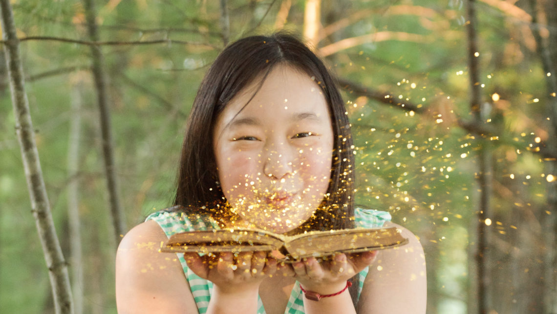 high school senior girl blows glitter off of a book