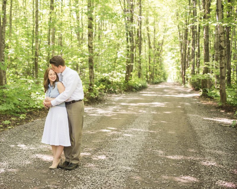 Husband and wife cuddle on a dirt road surrounded by trees