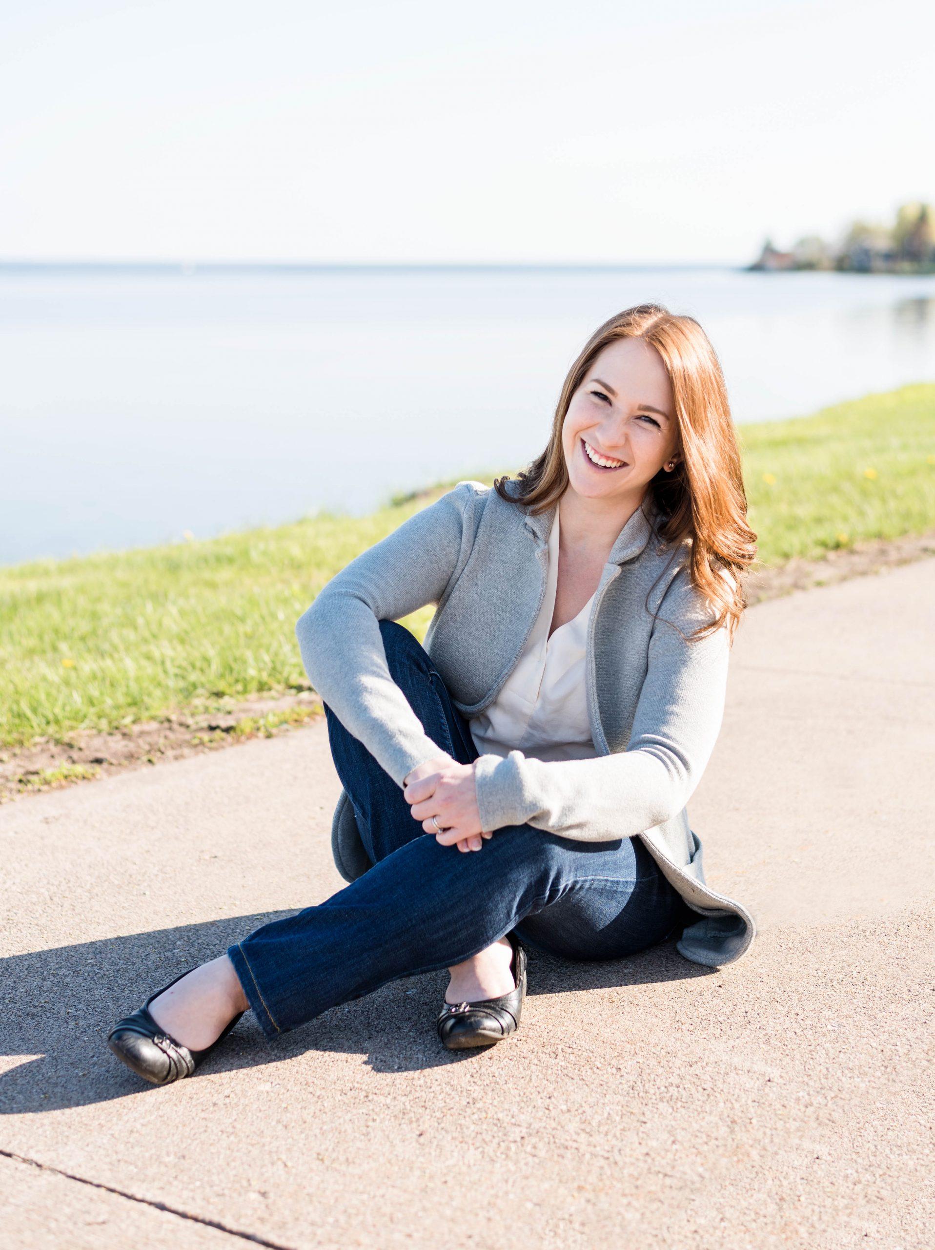 photographer sitting on a sidewalk near the bay