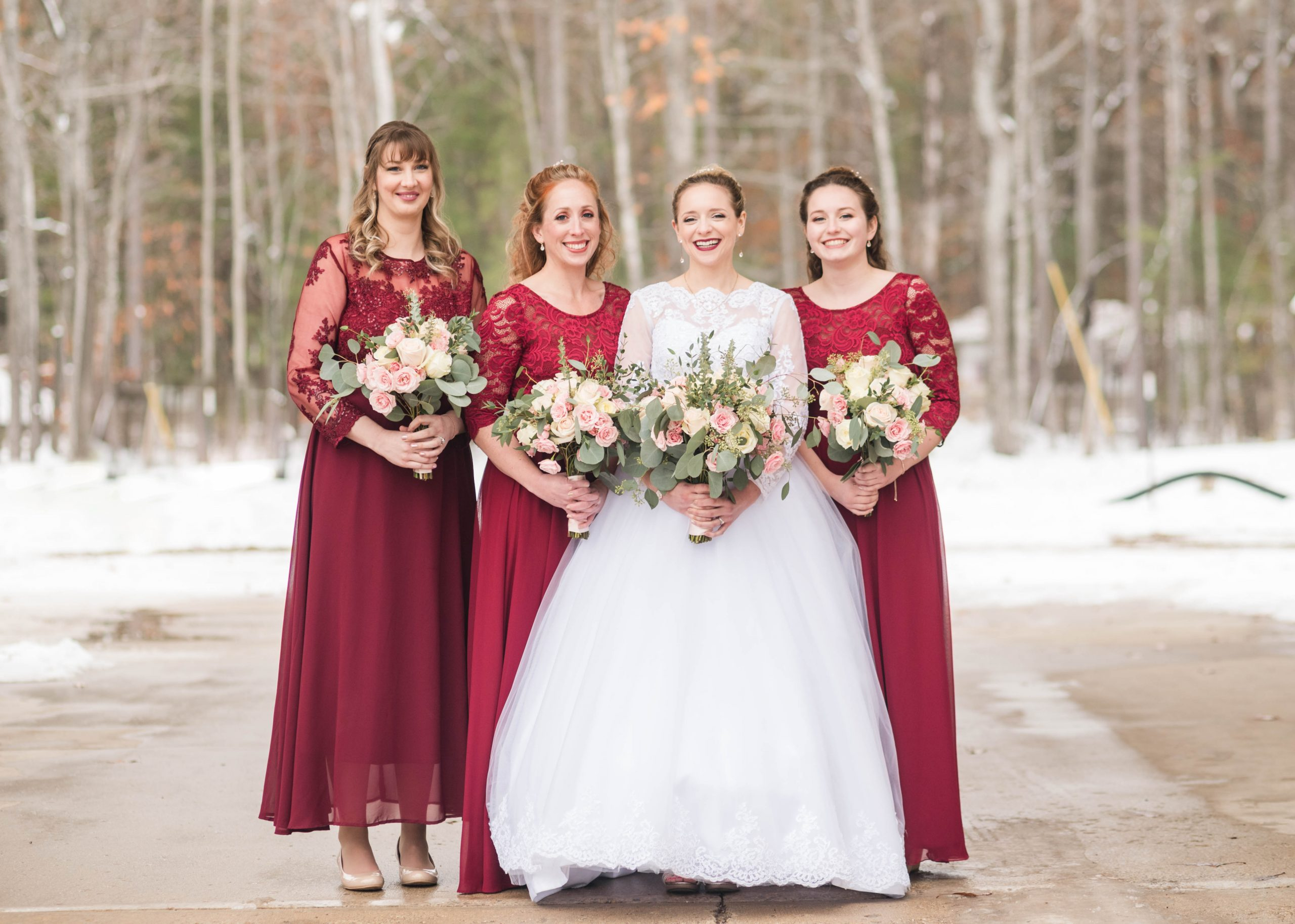 bride and bridesmaids smile together winter wedding