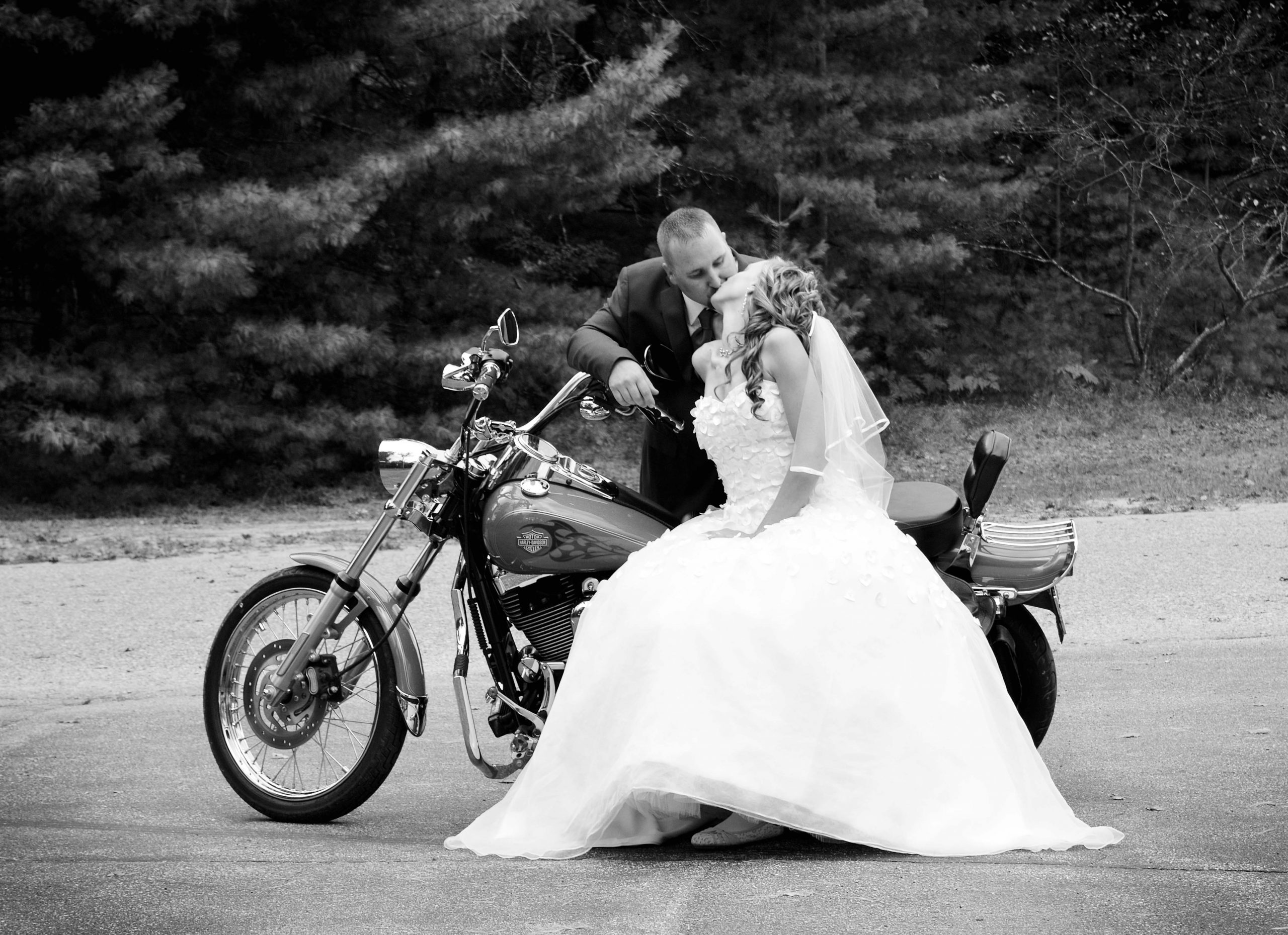 husband and wife kiss while sitting on a motorcycle