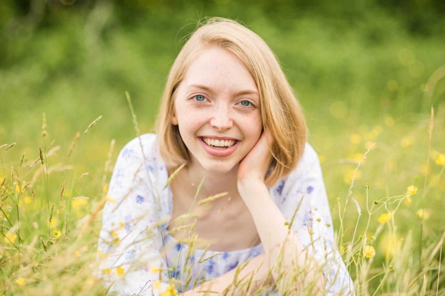 smiling blonde high school senior in field of wildflowers