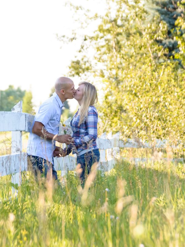 couple kiss in a country field near a fence
