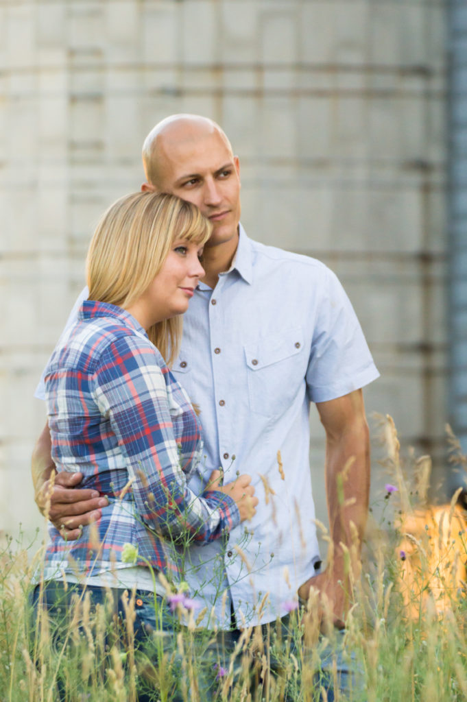 engaged couple hold each other in front of a barn silo