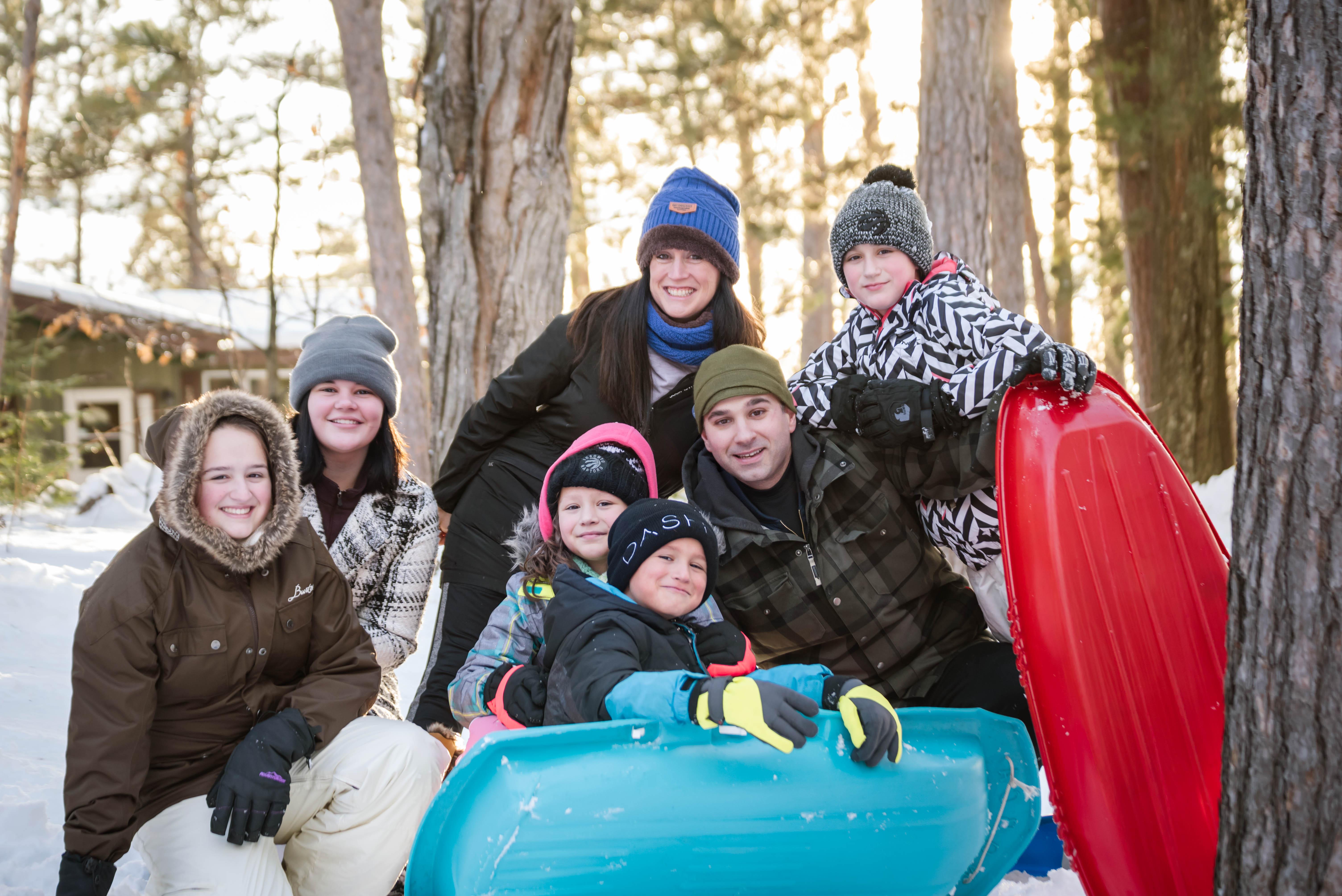 family enjoys time sledding together in dollar bay mi