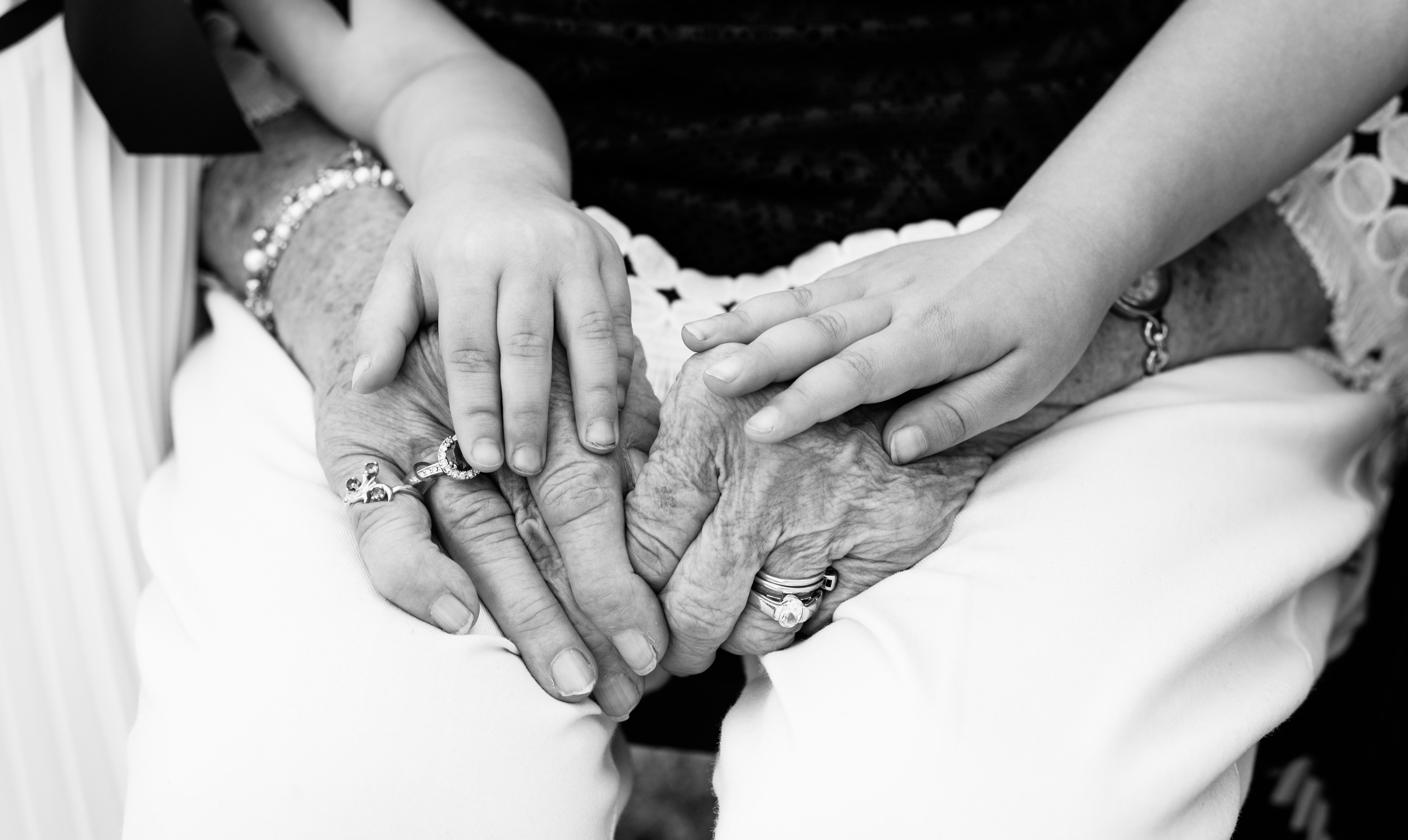 black and white image of grandmother's hands and grandchildren
