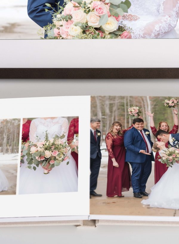 wedding album and framed print sit on a white desk