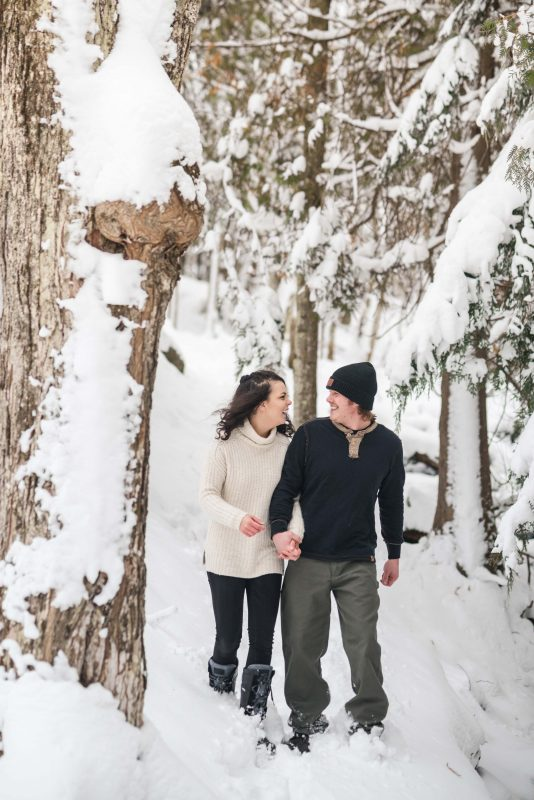 Husband and wife enjoy a snowy walk in the woods, winter engagement session in the upper peninsula