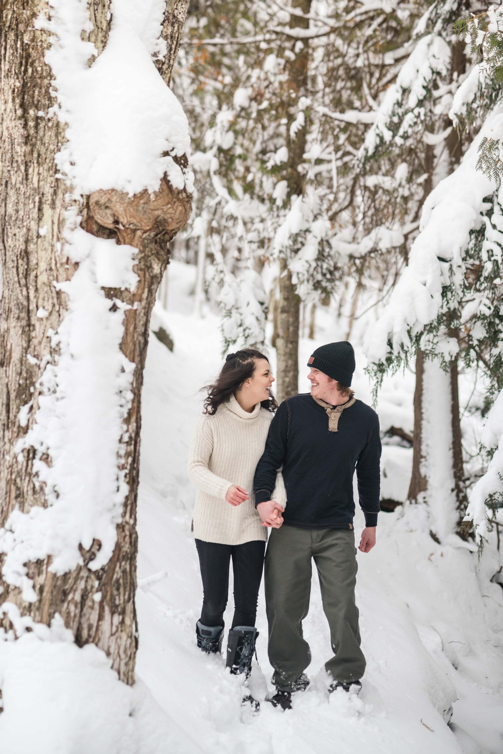 Husband and wife enjoy a snowy walk in the woods