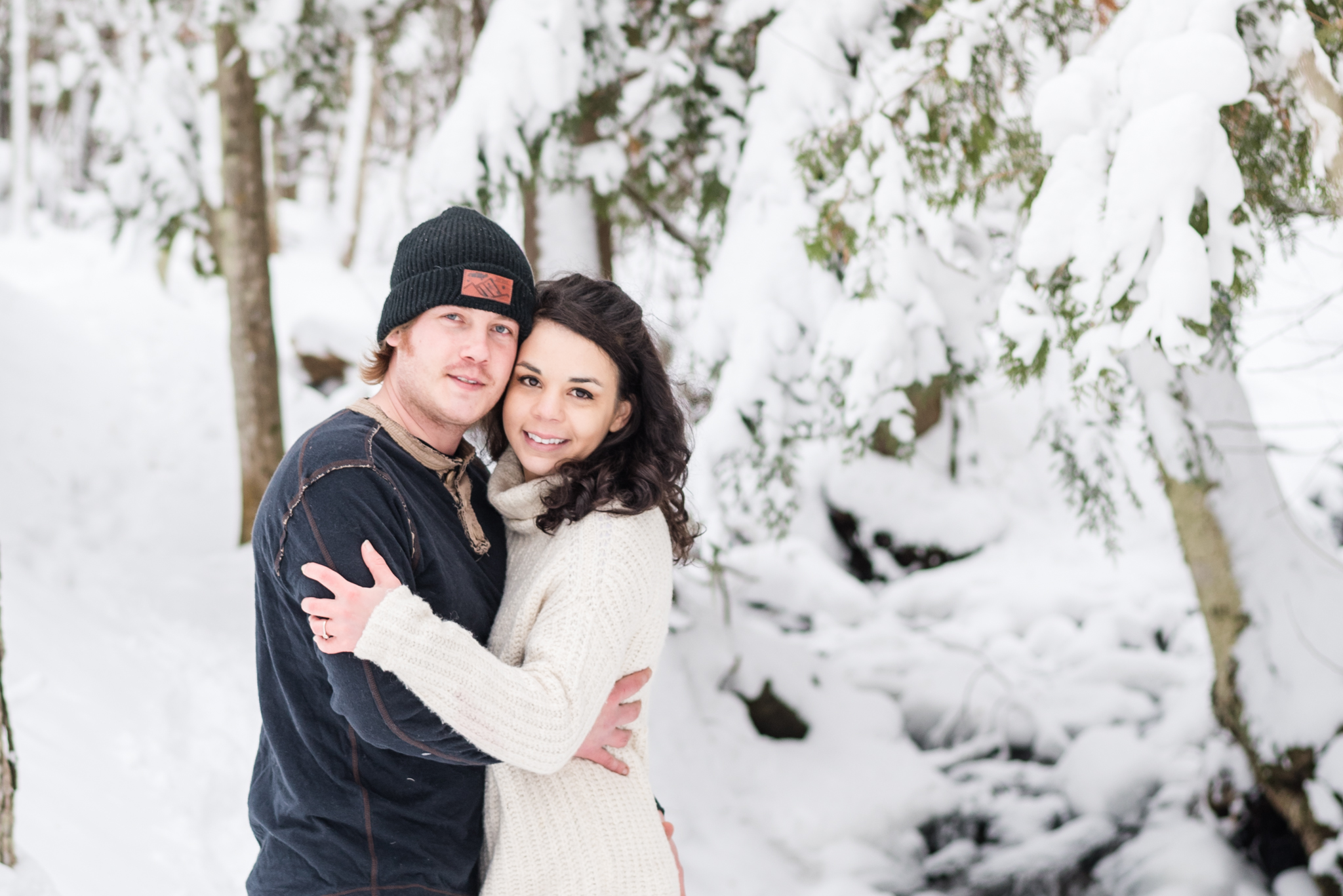husband and wife embrace in the snowy woods learn about planning a winter family photo session in the upper peninsula michigan