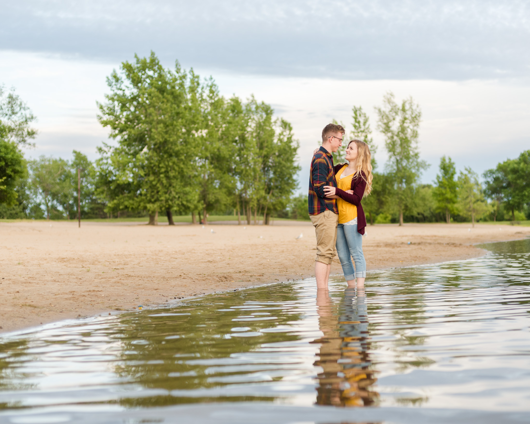 couple wearing jewel tones pose at beach for their engagement session in michigan