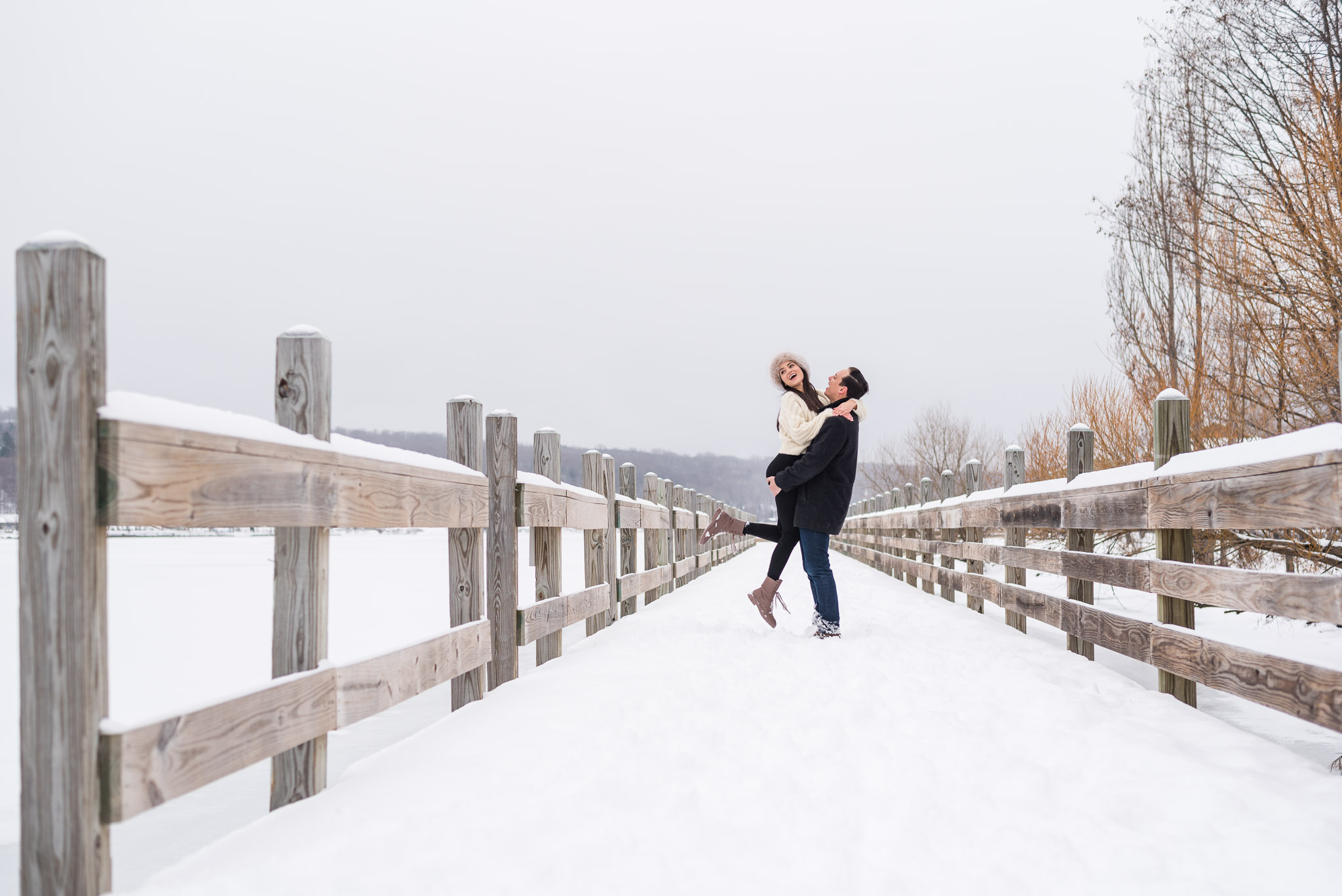 couple laughs together on a snow covered bridge