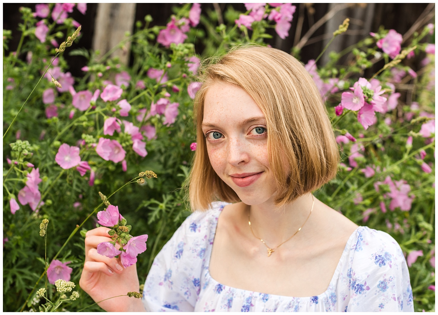 girl senior pictures with pink flower blossoms