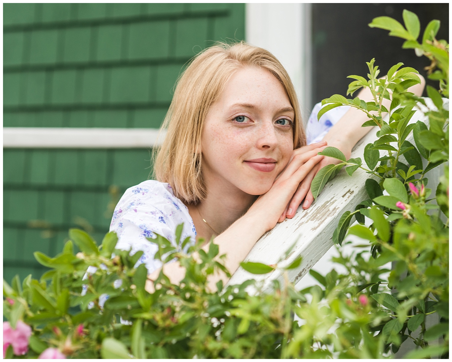 senior girl smiles softly as she leans on a railing at family farm