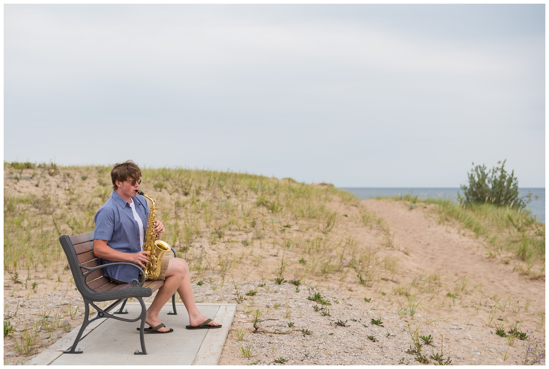 high school senior boy with saxophone on beach