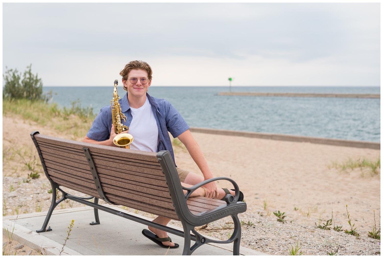 high school senior boy with saxophone at beach
